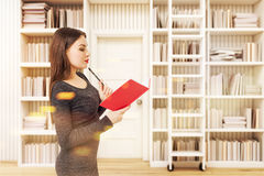 Vista lateral de una mujer en una biblioteca, entonada Imágenes de archivo libres de regalías