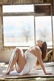 Vista lateral de una mujer joven relajada en vestido del apagado--hombro Foto de archivo libre de regalías