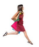Vista lateral de una mujer que salta con los panieres Foto de archivo libre de regalías