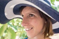 Vista lateral de una mujer que se coloca al aire libre en un azul de par en par brimmed imagenes de archivo