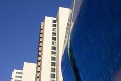 Vista lateral de una pared azul curvada de la ventana de cristal de un edificio alto corporativo moderno y elegante, al lado de u Foto de archivo libre de regalías