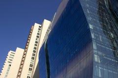 Vista lateral de una pared azul curvada de la ventana de cristal de un edificio corporativo moderno y elegante, al lado clásico a Fotografía de archivo