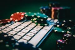 Vista lateral de una tabla verde del póker con algunas tarjetas del póker en un teclado Apuesta de concepto en línea imagen de archivo