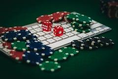 Vista lateral de una tabla verde del póker con algunas tarjetas del póker en un teclado Apuesta de concepto en línea imagenes de archivo