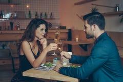 vista lateral de vidros do tinido dos pares do champanhe durante o jantar romântico Fotos de Stock