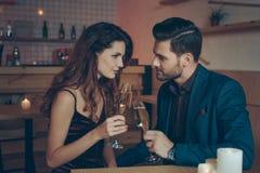 vista lateral de vidros do tinido dos pares do champanhe durante o jantar romântico Fotografia de Stock Royalty Free
