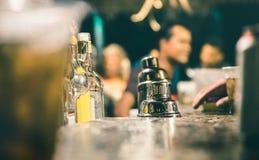 Vista lateral defocused borrosa del camarero en la barra del cóctel del bar imagenes de archivo