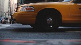 Vista lateral del ángulo bajo de la situación famosa del taxi del taxi del amarillo de Nueva York, entonces comenzando a moverse  metrajes