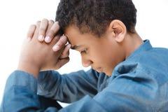 vista lateral del adolescente afroamericano pensativo que ruega con las manos en cerradura imagenes de archivo
