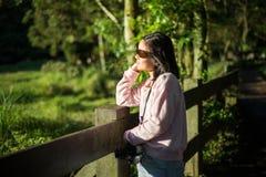 Vista lateral del adolescente asiático con las gafas de sol y de la cámara al lado del rancho Imagen de archivo