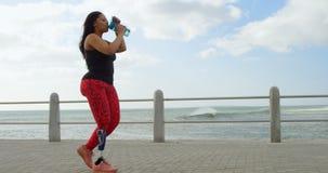 Vista lateral del agua potable de la mujer discapacitada en la 'promenade' 4k almacen de video