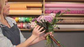 Vista lateral del artista floral de sexo femenino profesional que arregla el ramo hermoso en la floristería Ella es el combinar d almacen de metraje de vídeo