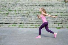 Vista lateral del atleta corriente joven deportivo activo del corredor de la mujer con el peso de la pérdida de la aptitud de la  imagen de archivo