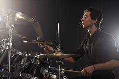 Vista lateral del batería joven Playing Drum Kit In Studio Foto de archivo libre de regalías