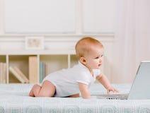 Vista lateral del bebé que se arrastra en cama hacia la computadora portátil Imagen de archivo