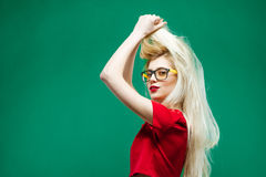 Vista lateral del Blonde que sorprende con el pelo largo y las lentes que presentan en fondo verde en estudio Fotos de archivo