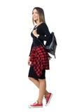 Vista lateral del bolso que lleva de la muchacha de moda joven del estudiante que camina y que mira para arriba Imágenes de archivo libres de regalías
