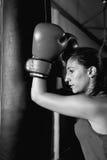 Vista lateral del boxeador de sexo femenino profesional en los guantes de boxeo que se inclinan en el saco de arena fotografía de archivo libre de regalías