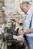Vista lateral del cerrajero que trabaja en la tienda dominante fotos de archivo