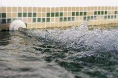 Vista lateral del chorro de agua inflowing en una piscina Fotos de archivo