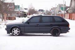 Vista lateral del coche familiar viejo, negro, alemán en invierno Imágenes de archivo libres de regalías