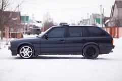 Vista lateral del coche familiar viejo, negro, alemán en invierno Foto de archivo libre de regalías