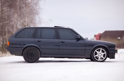 Vista lateral del coche familiar viejo, negro, alemán en invierno Imagen de archivo libre de regalías