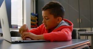 Vista lateral del colegial asiático atento que estudia con el ordenador portátil en sala de clase en la escuela 4k almacen de video