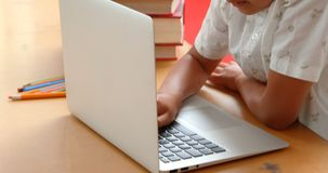 Vista lateral del colegial asiático atento que estudia con el ordenador portátil en una sala de clase en la escuela 4k metrajes