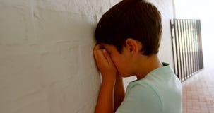 Vista lateral del colegial caucásico que cubre su cara con las manos mientras que se inclina en la pared en el pasillo 4k metrajes