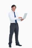 Vista lateral del comerciante sonriente con su computadora portátil Foto de archivo