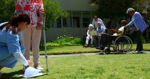 Vista lateral del doctor de sexo femenino que examina al paciente mayor en el jardín de la clínica de reposo 4k metrajes