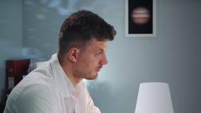 Vista lateral del doctor hermoso en la capa blanca que escucha el paciente almacen de video