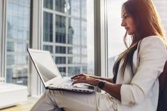 Vista lateral del empresario de sexo femenino confiado que usa el ordenador portátil que se sienta en centro de negocios moderno foto de archivo libre de regalías