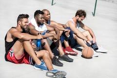 vista lateral del equipo de baloncesto multicultural que descansa después de juego imágenes de archivo libres de regalías