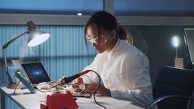 Vista lateral del especialista afroamericano de la electrónica que trabaja con el probador del multímetro y otros dispositivos el almacen de metraje de vídeo