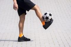 Vista lateral del fútbol del estilo libre o del ingenio de la bola del jugador que hace juegos malabares futsal imagenes de archivo