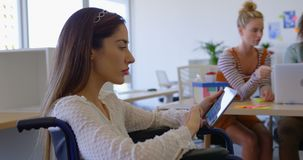 Vista lateral del funcionamiento discapacitado caucásico joven de la hembra en la tableta digital en la oficina moderna 4k almacen de metraje de vídeo