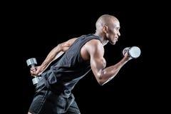Vista lateral del funcionamiento muscular del hombre mientras que lleva a cabo pesa de gimnasia Foto de archivo