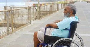 Vista lateral del hombre afroamericano mayor activo discapacitado pensativo en silla de ruedas en la 'promenade' 4k metrajes