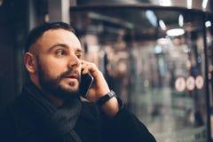 Vista lateral del hombre barbudo joven, desgaste incasual vestido, él se está colocando en la calle y está utilizando un smartpho Imagen de archivo libre de regalías
