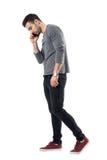 Vista lateral del hombre casual joven serio que camina y que habla en el teléfono que mira abajo Foto de archivo libre de regalías