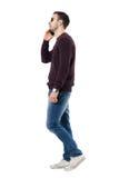 Vista lateral del hombre casual joven serio que habla en el teléfono que mira lejos Foto de archivo