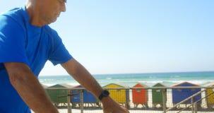 Vista lateral del hombre caucásico mayor activo que comprueba tiempo en smartwatch en una 'promenade' en la playa 4k metrajes