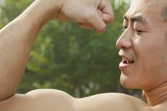 Vista lateral del hombre confiado muscular que muestra apagado y que dobla su bíceps Imágenes de archivo libres de regalías