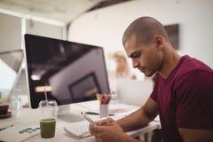 Vista lateral del hombre de negocios joven usando el teléfono móvil mientras que se sienta en el escritorio Imagenes de archivo