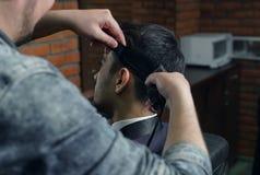 Vista lateral del hombre en el traje que consigue corte de pelo del peluquero en la barbería Foto de archivo