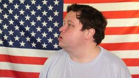 Vista lateral del hombre gordo joven en el fondo de una bandera de los E.E.U.U. almacen de metraje de vídeo
