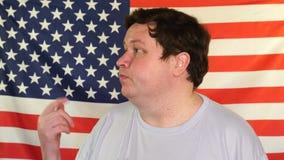 Vista lateral del hombre gordo joven que invita alguien en el fondo de una bandera de los E.E.U.U. almacen de video