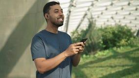 Vista lateral del hombre joven que escucha la música y el exterior de baile almacen de metraje de vídeo